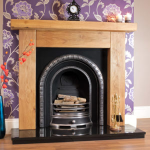 Ashford rustic oak beam fireplace shown in a light oak finish with a Henley cast iron arch insert and a solid fuel basket